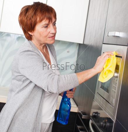 Женщина чистит кухню