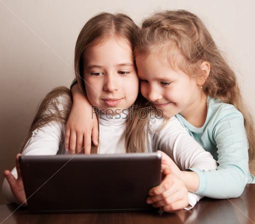 Дети, играющие на планшете