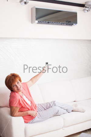 Женщина держит пульт дистанционного управления кондиционером