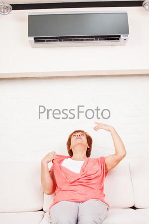 Женщина сидит под кондиционером