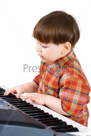 Мальчик учится играть на синтезаторе