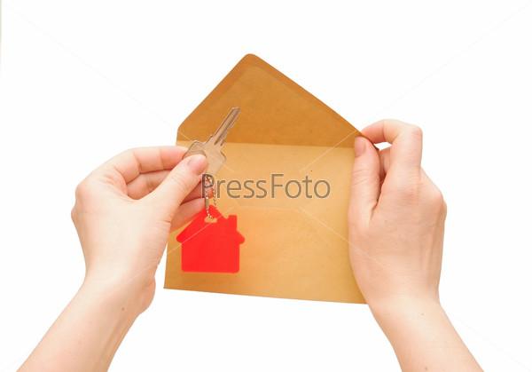 Ключ с красным символом дома на цепочке в руке на белом фоне