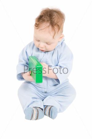 Фотография на тему Ребенок играет с зеленым пластиковым блоком
