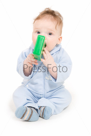 Ребенок играет с зеленым пластиковым блоком