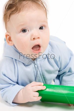 Ребенок играет с зеленым пластиковым кубиком на полу