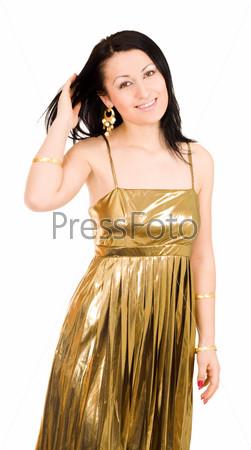 Счастливая женщина стоит в золотом платье и гладит волосы