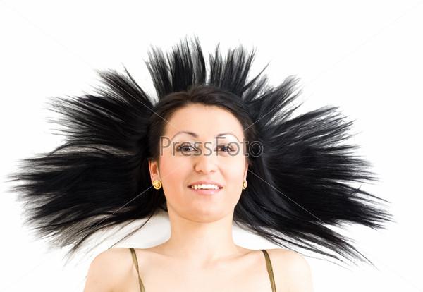Спокойная и улыбающаяся женщина с длинными черными волосами лежит на полу