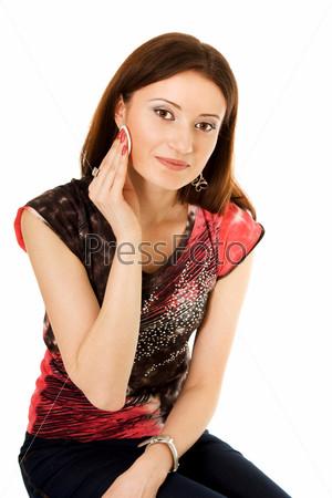 Женщина смывает макияж ватным тампоном, глядя в камеру
