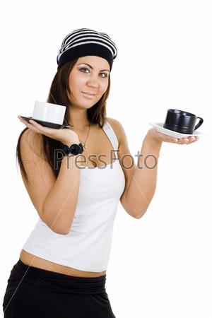 Женщина в белом топе и черных брюках, держащая черно-белые чашки как весы
