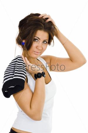 Женщина с полосатой шапкой держит себя за волосы и мило смотрит камеру, полубоком