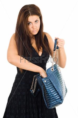 Фотография на тему Молодая женщина с длинными волосами ищет что-то в синей сумочке рукой, глядя в камеру