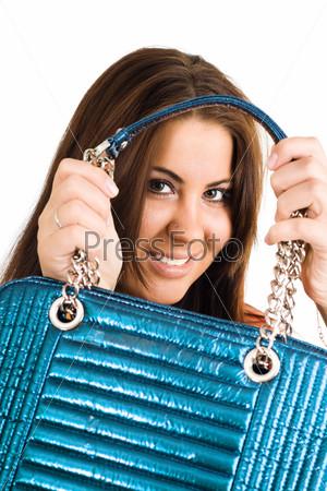Фотография на тему Молодая женщина держит синюю сумочку двумя руками, глядя в камеру