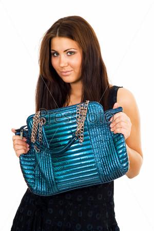 Молодая женщина держит синюю сумочку двумя руками, глядя в камеру