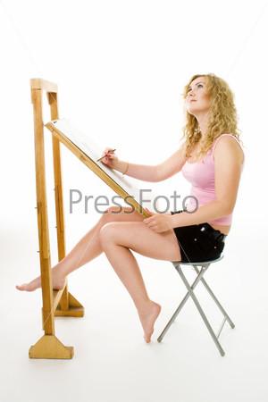 Женщина рисует картину на мольберте, сидя в профиль
