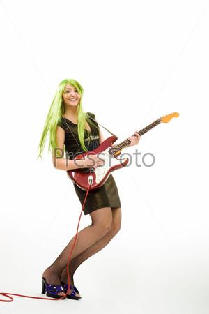 Молодая женщина с длинными цветными волосами играет на красной гитаре