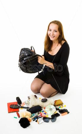 Фотография на тему Женщина сидит на полу рядом с содержимым своей сумки и улыбается