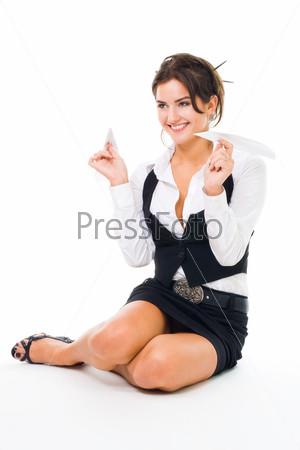 Бизнес-леди играет с бумажным самолетом, сидя на полу, изолированная на белом фоне