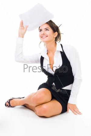 Фотография на тему Счастливая девушка в строгой одежде смотрит вверх, сидя на полу и держа документ