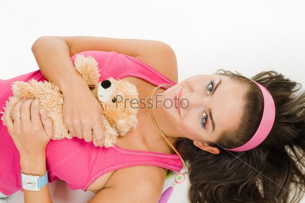 Молодая женщина с игрушкой лежит на полу