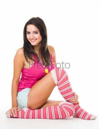 Фотография на тему Женщина с длинными волосами сидит в розовых носках и смотрит в камеру, изолированная на белом фоне