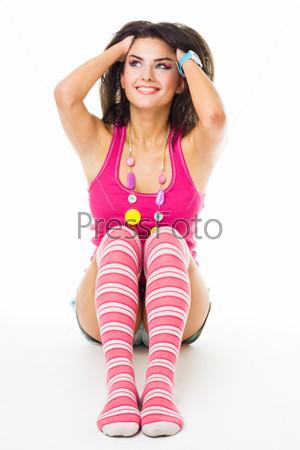 Молодая женщина сидитт на полу, поправляя волосы с улыбкой, изолированная на белом фоне