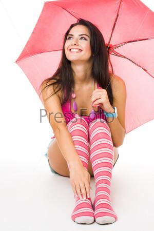 Счастливая девушка в розовом сидит с зонтом, изолированная на белом фоне