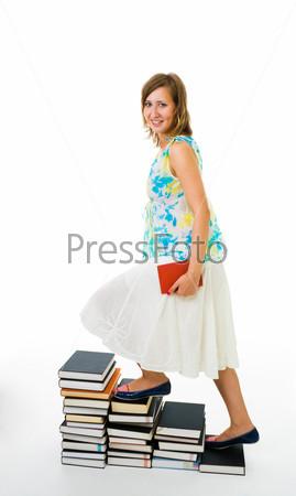 Молодая женщина, поднимающаяся на лестницу из книг