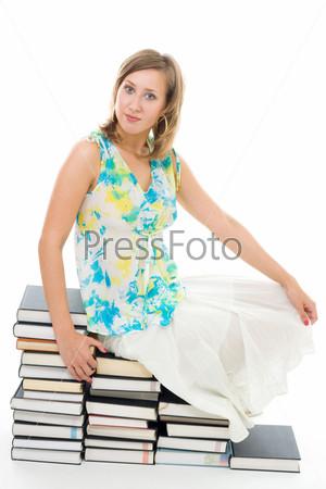 Молодая женщина в летней одежде сидит на книгах, глядя в камеру и улыбаясь