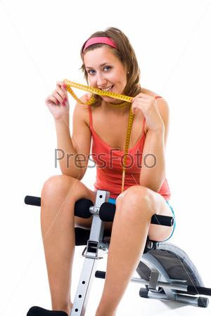 Фотография на тему Улыбающаяся женщина сидит с сантиметром на скамье для пресса после фитнеса