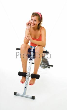 Молодая женщина говорит по телефону на скамье для упражнений на пресс