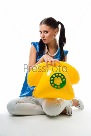 Счастливая молодая девушка с надувным детским телефоном