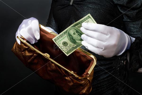 Женщина в белых перчатках кладет банкноту в кошелек