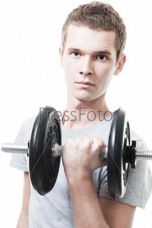 Молодой человек, поднимающий тяжести в тренажерном зале