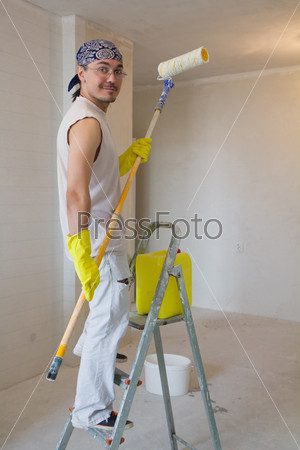 young worker painting ceiling with painting roller
