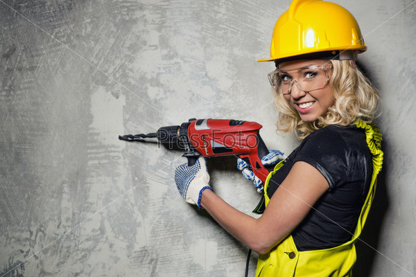 attractive builder woman with a drill in her hands. Black Bedroom Furniture Sets. Home Design Ideas