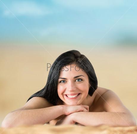 Красивая женщина в бикини загорает на берегу моря