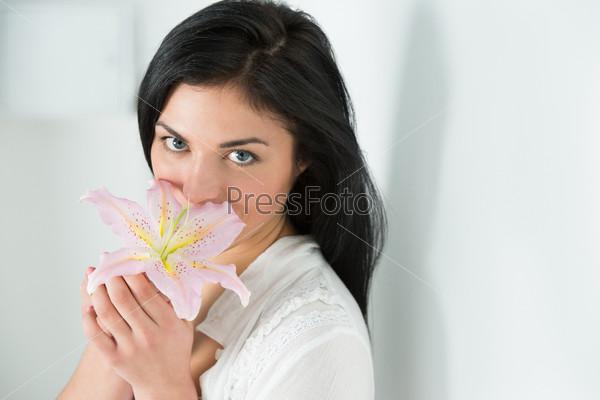Фотография на тему Привлекательная молодая женщина держит цветок лилии