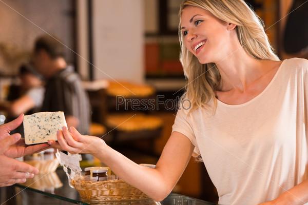 Женщина покупает сыр в продуктовом магазине
