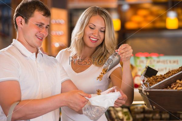 Продуктовый магазин - счастливая пара делает покупки в супермаркете