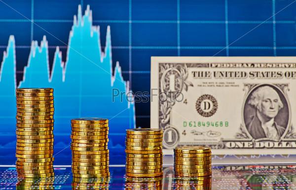 Падающие финансовые диаграммы, долларовая банкнота, стопки золотых монет