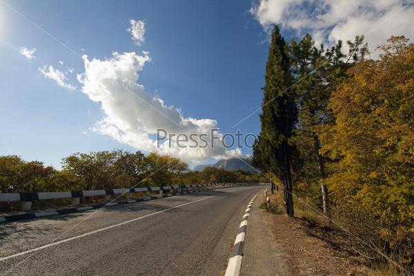 Автомагистраль в осеннем лесу с видом на Крымские горы
