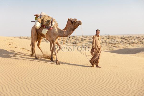 Бедуин и верблюд в песчаных дюнах в пустыне