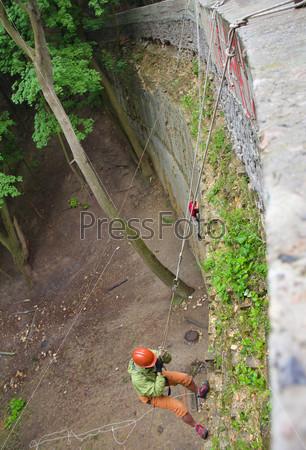 Фотография на тему Альпинист поднимается на бетонную стену