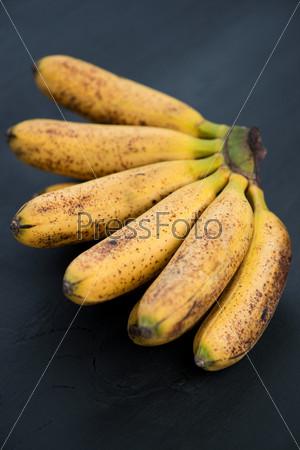 Тайские спелые бананы на темном фоне