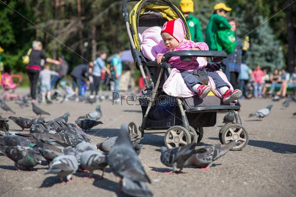 Девочка играет с голубями в улице города
