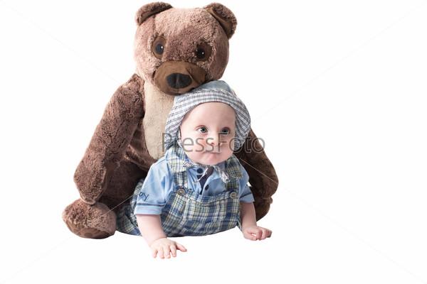 Прелестный мальчик с игрушечным медведем, изолированный на белом фоне