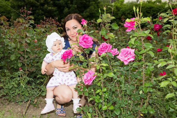 Счастливая мама и ребенок в цветах. Концепция детства и семьи