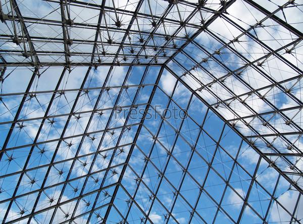 Часть металлической конструкции крыши со стеклом на фоне голубого неба