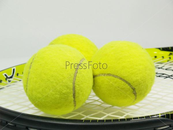 Теннисная ракета и три желтых мяча на сером фоне