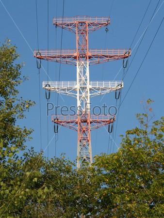 Красно-белая металлическая опора линии электропередачи на фоне голубого неба